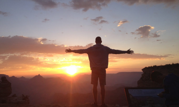 Male standing in the Grand Canyon at sunrise